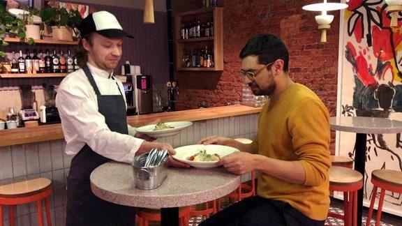 Mann in Kochmontur serviert dunkelhaarigem Mann in gelbem Pullover ein Essen.