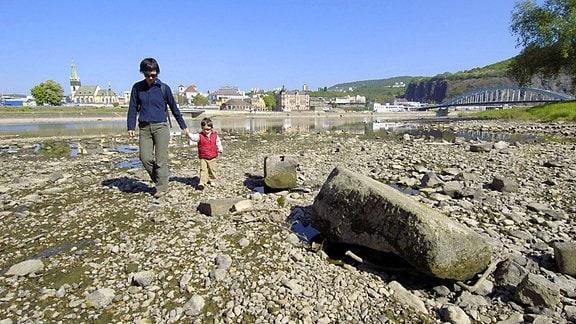 Eine Mutter und ein Kind laufen über trockenen Boden