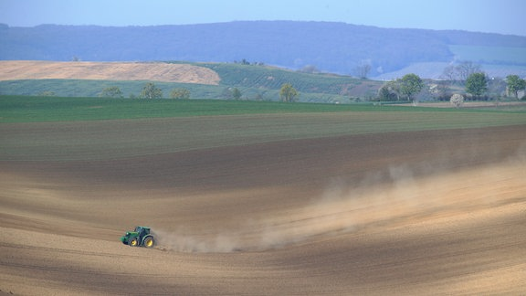 Ein Traktor fährt über ein staubtrockenes Feld