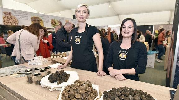 Ausstellerinnen stehen vor Trüffeln auf Tellern auf der Trüffelmesse in Livade.