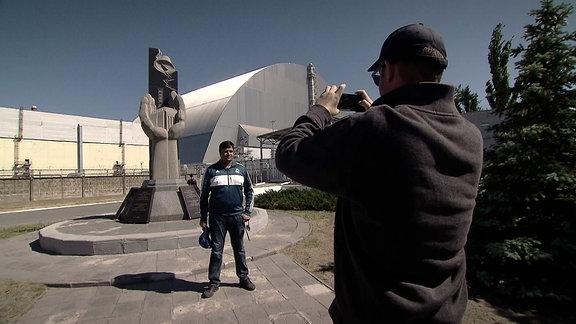 Ein Mann lässt sich vor Denkmal fotografieren