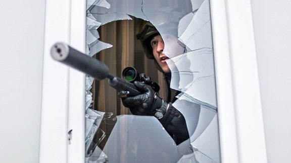 Scharfschütze schaut aus einem Fenster. Das Gewehr trägt einen Schalldämpfer.