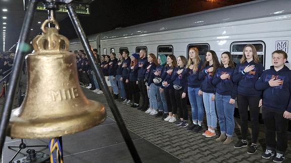 Junge Menschen stehen auf einem Bahnsteig neben einem Zug, daneben eine Glocke