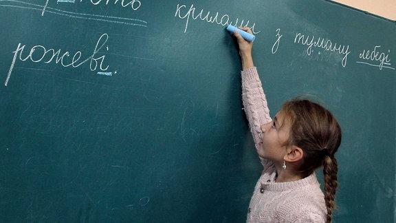 Ein Mädchen schreibt an die Tafel in Ukrainisch