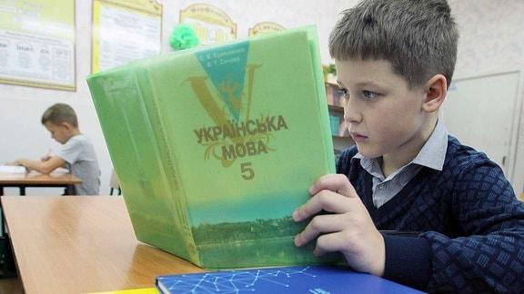 Ein Junge liest in einem ukrainischen Schulbuch