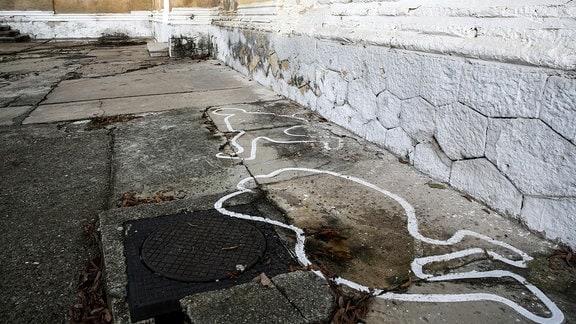 Wand mit Einschüssen und Markierungen auf dem Boden, die Personenumrisse zeigen