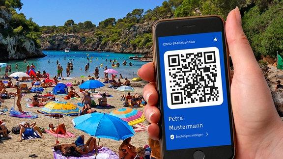 Symbolbild: Ein digitaler Impfpass auf dem Smartphone vor einem Strand mit vielen Besuchern.