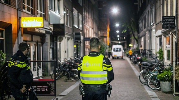 Polizisten stehen in einer kleinen Straße, links und rechts Häuser.