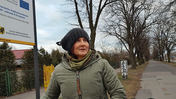 Eine Frau mit Mütze und dicker Jacke steht mit einem Fahrrad auf einem Radweg neben einem Baustellenschild der EU