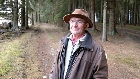 Ein älterer Mann mit Filzhut und Lederjacke steht im Wald