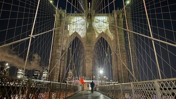 Während einer -Gedenk-Zeremonie wurden Bilder von New Yorkern, die durch die Pandemie verloren gegangen waren, auf die Brooklyn Bridge projiziert.
