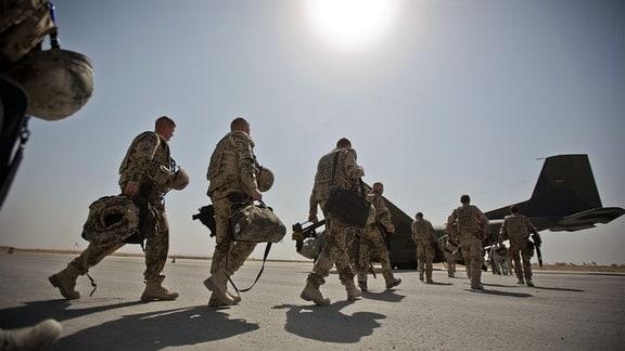 Bundeswehrsoldaten gehen zu einer Transportmaschine vom Typ Transall C-160.