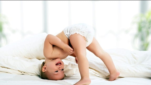 Ein vergnügtes Baby mit Windel macht in einem Bett einen halben Kopfstand.