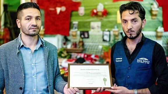 Izzet Cagac (l), der bisherige Betreiber des Imbisses «Kiez-Döner», hält bei der Wiedereröffnung die Geschenk- und Abtretungsvereinbarung an den neuen Betreiber Ismet Tekin (r).