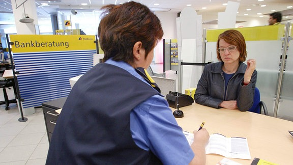 Postbankangestellte und Kundin beim Beratungsgespräch.