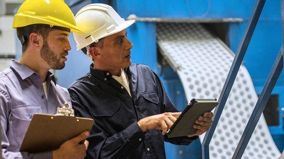 Zwei Ingenieure beraten sich an einer Maschine.