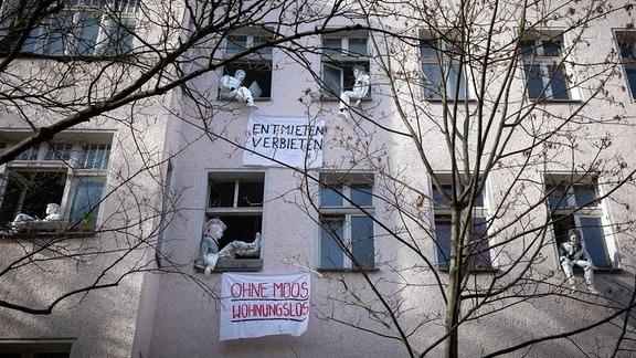 Gipspuppen und Banner als Mieterprotest und Kunstaktion an Fenstern eines Hauses