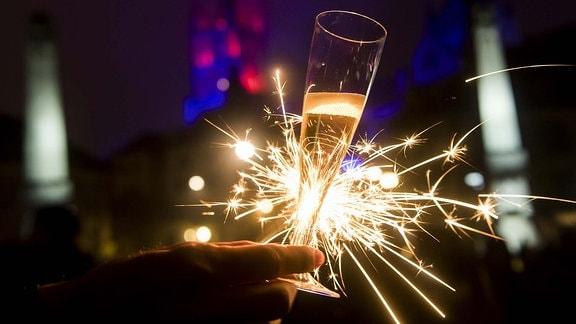 Mit einem Glas Champagner und einer Wunderkerze in der Hand steht eine Frau.