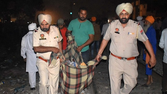 Police carrying a dead body after a train accident, on October 19, 2018 in Amritsar, India.