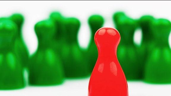 eine rote Figur gegenüber vielen grünen Figuren