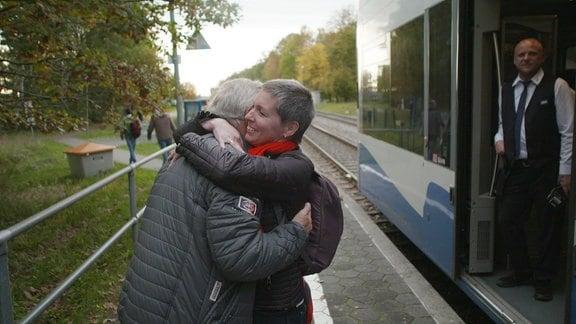 Zwei Menschen begrüßen sich am Bahnhof.