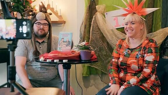 Ein Mann und eine Frau drehen ein Video weihnachtlich geschmückt