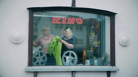 Zwei Frauen sind durch ein Fenster in einem Kino zu sehen