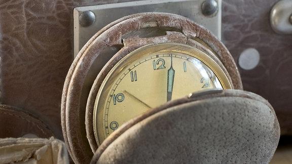 Eine alte Taschenuhr vor einem Koffer.