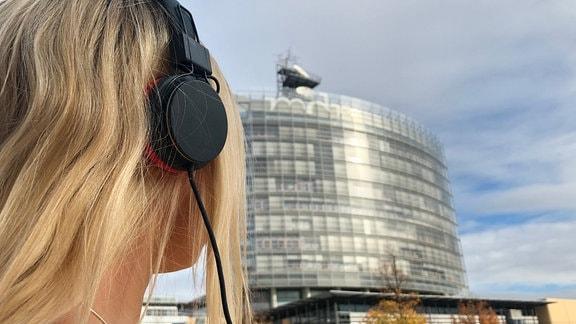 Eine Frau mit Kopfhörern steht vor dem MDR-Hochhaus.