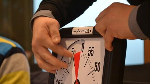 Eine Hand bewegt einen Zeiger auf einer großen Workshop-Uhr.