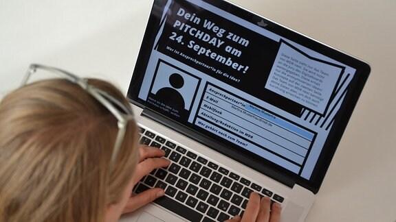 Eine Frau füllt ein Formular am Computer aus.