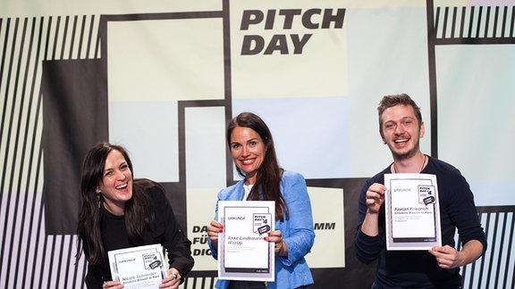 Zwei Frauen und ein Mann halten lachend je eine Urkunde in die Kamera.