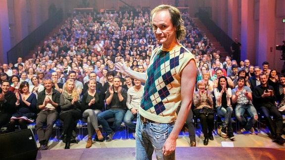 Olaf Schubert auf der Bühne. Im Hintergrund lachende Zuschauer im Saal.