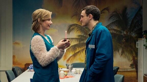 Christian (gespielt von Franz Rogowski) schenkt  Marion (gespielt von Sandra Hüller) einen Geburtstagskuchen.