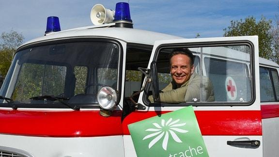 """""""Hauptsache gesund""""-Moderator Dr. Carsten Lekutat lehnt aus dem Fenster eines DDR-Rot-Kreuz-Barkas"""