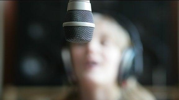 Ein Junges Mädchen hinter einem Mikrofon im Studio.