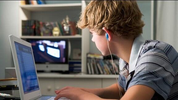 Jugendlicher, mit Kopfhörern im Ohr, sitzt vor einem Laptop und schaut auf einen Ferseher