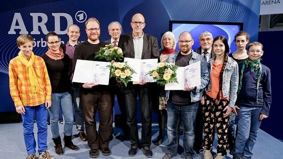 Felix Kästner (Kinderjury), Katrin Richter, Nico Eppert (beide Expertenjury), Jens Raschke (Preisträger Platz 2), Dr. Gerhart Pasch (Jurymitglied seitens des Rundfunkrates), Jörgpeter von Clarenau (Preisträger Platz 1), Dr. Christina Seidel (Expertenjury), Thilo Reffert (Preisträger Platz 2), Peter Heinzel (Jurymitglied seitens des Rundfunkrates), Selma Roth, Lal Lucie Kreusch, Jonathan Kästner (alles Kinderjury) (v.l.)