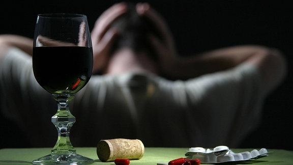 Ein Mann wendet sich ab. Vor ihm steht ein Rotweinglas.