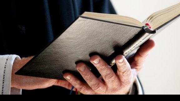 Ein Priester hält ein aufgeschlagenes Buch in den Händen.