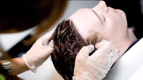 Einem jungen Mann werden die Haare gefärbt.