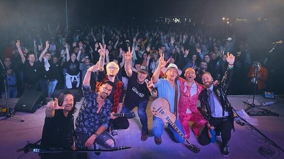 Mehrere Musiker auf einer Bühne, im Hintergrund Publikum