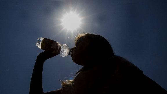 Eine Frau trinkt vor einer strahlenden Sonne aus einer Wasserflasche.
