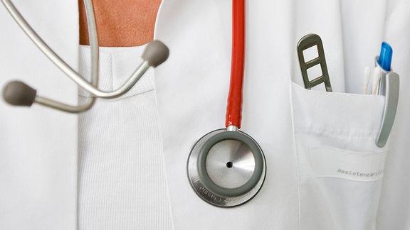 Ein Stethoskop hängt um den Hals einer Frau im Arztkittel