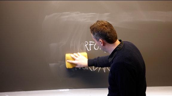 Lehrer wischt eine Tafel ab.