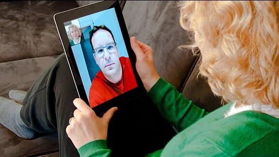Eine Frau sitzt mit einem Tablet PC auf einem Sofa und unterhält sich per Videochat mit einem Mann.