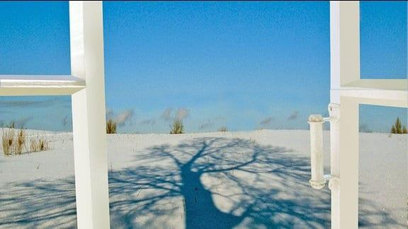 Ein geöffnetes Fenster mit Blick auf eine Winterlandschaft und stahlblauen Himmel.
