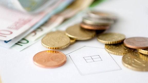 Geld liegt auf einem Hausplan