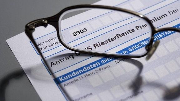 Eine Brille auf einem Antrag zur Riesterrente