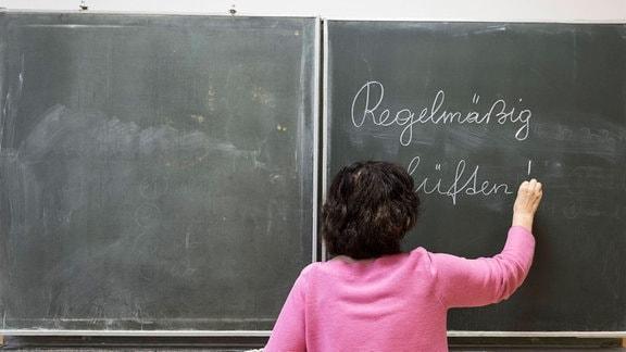 Lehrerin schreibt auf Tafel,